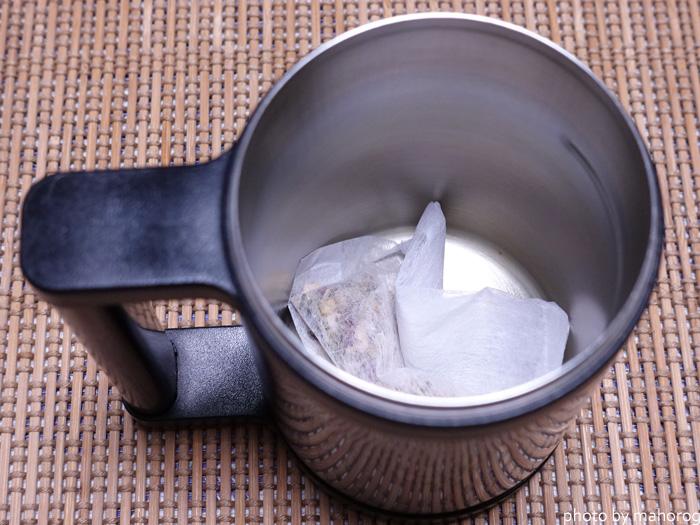 ハーブティーのティーパックを入れたマグカップ